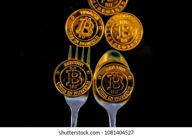 Black food plate, with spoon and golden bitcoin on black background, abstract business concept of modern business, comparable bitcoin, like food to eat.