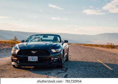 Black Ford Mustang GT convertible  is parked by the infinite long road in the middle of a death valley in Nevada, USA. August 30, 2017