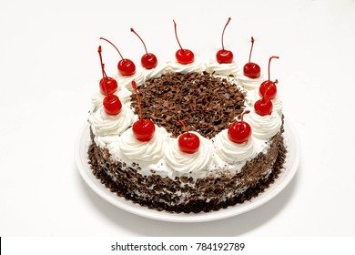 Black forest cake decorated with whipped cream, chocolate and marachino cherries. Schwartzwald cake