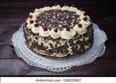 Black Forest cake on mahogany wood background.