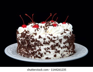 black forest cake on an off white plate isolated on a dark background. Whipped cream, shaved chocolate candy, cherries on top.