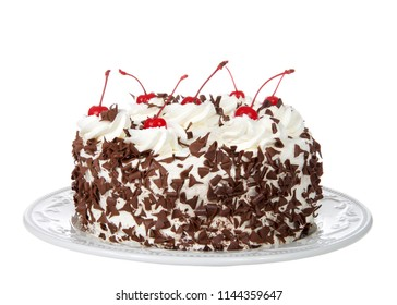 black forest cake on an off white plate isolated on a white background. Whipped cream, shaved chocolate candy, cherries on top.