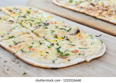 Black Forest speciality called Flammkuchen in south Germany and Tarte flambee in northeast France - vegetarian - on wooden platter