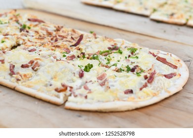 Black Forest speciality called Flammkuchen in south Germany and Tarte flambee in northeast France - traditional topping - on wooden platter