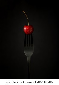 Black fork with a red cherry with water drops on black background and. Card with copy space