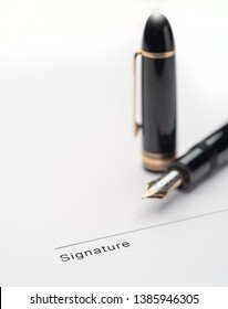 Black fountain pen on document pointing to signing area