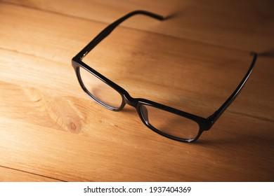 black frame eye glasses on wooden desk