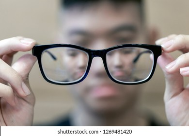 The Black frame glasses on the hands of boys with short-sighted eyes in front,Concepts of short-sighted children from playing games all the time