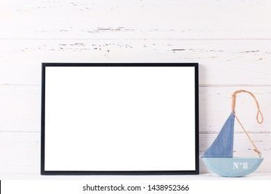 Black  frame mockup  with copy space and  summer sea vacation  decorations by  wooden white wall. l Landscape orientation.