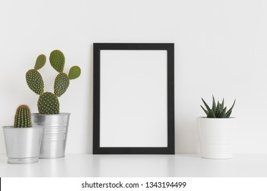 Black frame mockup with various types of cactus and a succulent plant on a white table. Portrait orientation.