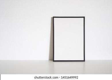 Black frame poster on table in white room