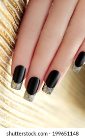 Black French manicure with Golden shining varnish on striped background