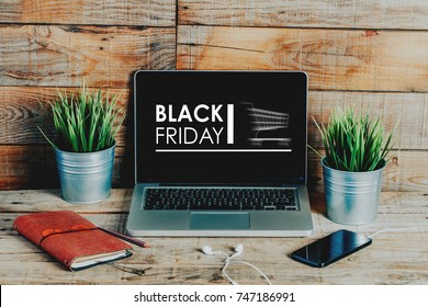 Black friday advertisement in a laptop computer screen placed on a wooden desk.