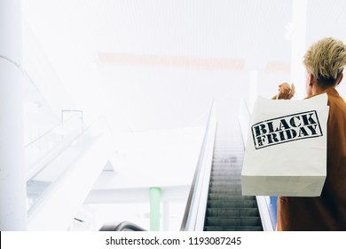Black Friday. Back view of a girl holds paper shopping bags near an escalator in a mall. Indoor shoot. Copy space area available.