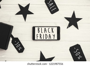 Black Friday big sale text on phone screen. Special discount christmas offer. Phone with advertising message at gift boxes and price tags. Stylish minimalistic flat lay. Shopping time