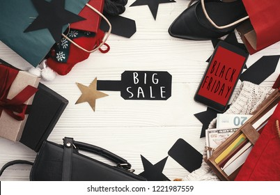 Black Friday big sale text on phone screen, flat lay. Special discount christmas offer. Phone with advertising message at money, wallet, bags, clothes, gift boxes, price tags. Shopping time