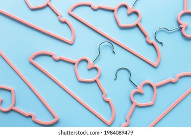 Black Friday or clothing industry concept on blue background flat lay with randomly scattered pink clothes hangers pattern