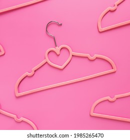 Black Friday or clothing industry concept on pink background flat lay with randomly scattered pink clothes hangers pattern with heart shape on hanger