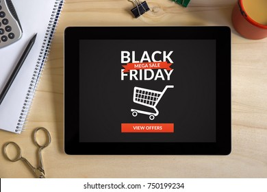 Black friday concept on tablet screen with office objects on wooden desk. All screen content is designed by me. Top view