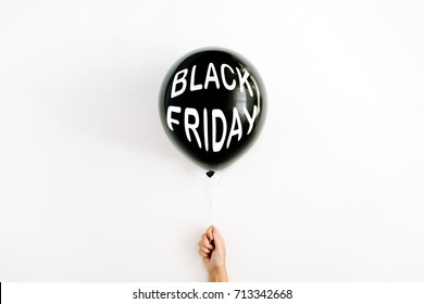 Black Friday concept. Quote Black Friday on black balloon in girl's hand. Flat lay, top view. Black Friday background.