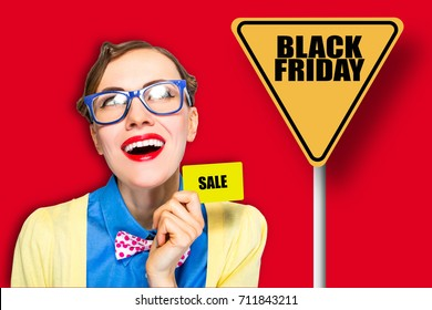 Black friday crazy woman wearing glasses holding plastic card looking sideways over vibrant red background