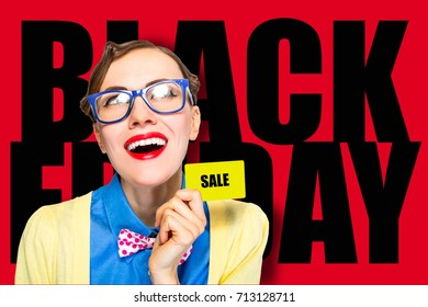 Black friday crazy woman wearing glasses holding credit card looking sideways