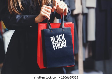 Black Friday! Elegant rich woman wearing fashion trench-coats showing shopping black friday bag in fashion mall after great shopping process, concept of consumerism, sale, rich life