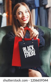 Black Friday! Elegant rich woman wearing fashion trench-coats sitting in the armchair and showing shopping bags in fashion mall after great shopping process, concept of consumerism, sale, rich life