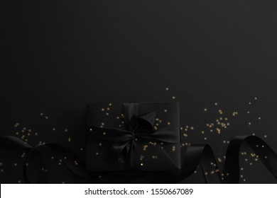 Black friday gift, paper box with silk ribbon bow and golden glitter stars on black paper background with copy space for text, flat lay top view template