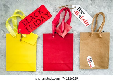 Black friday labels near paper shopping bag on grey background top view