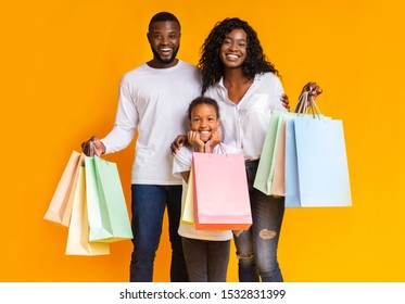 Black Friday. Portrait of smiling african american family with paper bags happy after successful shopping, yellow studio background