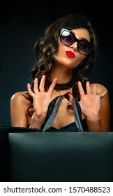 Black friday sale concept. Closeup portrait of girl for shop ads. Woman in sunglasses holding big bag isolated on dark background at shopping.