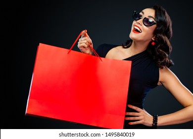 Black Friday sale concept for shop. Happy smiling girl in sunglasses holding big red bag isolated on dark background at shopping. Woman pointing to looking on copy space for sales text.