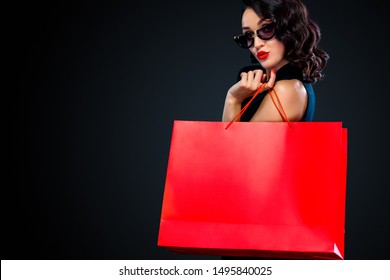Black Friday sale concept for shop. Shopping woman in sunglasses holding red bag isolated on dark background.