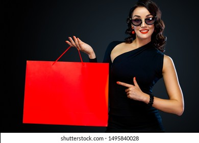 Black Friday sale concept for shop. Shopping girl in sunglasses holding red bag isolated on dark background. Woman pointing to looking left on copy space.