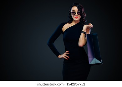 Black Friday sale concept for shop. Happy smiling girl in sunglasses holding big bag isolated on dark background at shopping.
