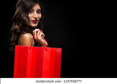 Black friday sale concept. Shopping woman holding red bag isolated on dark background in holiday