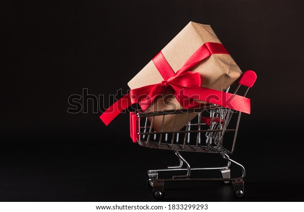 Black Friday Sale concept, Top view of gift box wrapped brown paper and red bow ribbon present in the shopping cart, studio shot on dark background