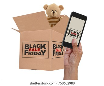 Black Friday Sale on cell phone screen held by hand in front of cardboard box with teddy bear white background