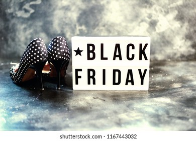 Black friday sale word on lightbox on black surface, top view to women shoes