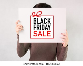 Black Friday Sales concept: A beautiful woman holding a white board showing