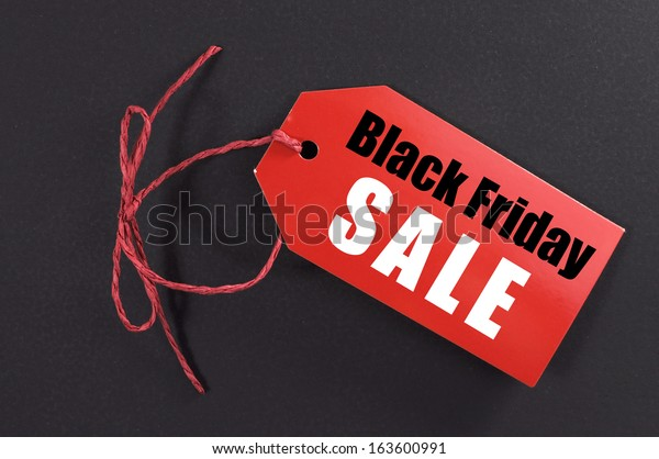 Black Friday shopping sale concept with red ticket Sale tag close up on black background.