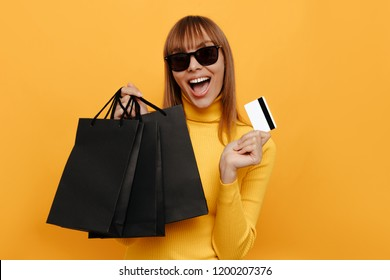 Black friday. Shopping. Woman portrait. Cheerful girl is holding black shopping bags and a credit card and smiling, on a yellow background