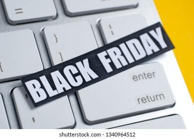 Black Friday sticker on a white keyboard. Yellow background.