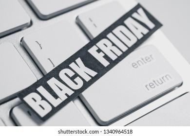 Black Friday sticker on white keyboard. Black and white photo.