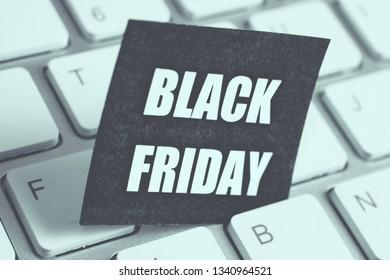 Black Friday sticker on white keyboard. Toned, Close up.
