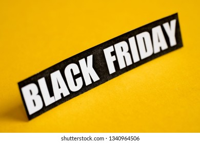 Black Friday sticker on a yellow background. Close up.