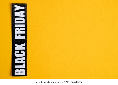 Black Friday sticker on a yellow background. Close up. Copy space.