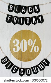 Black Friday thirty percent Discount paper banner garland lettering hanging on white barn wood planks background. Luxurious vertical holiday flyer.