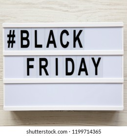 'Black friday' word on lightbox over white wooden background, overhead view. Flat lay, from above, top view.